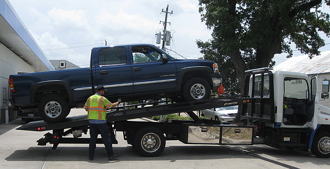 image of a blue truck being towed