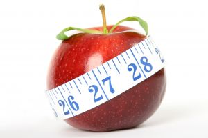 red apple with measuring tape surrounding it