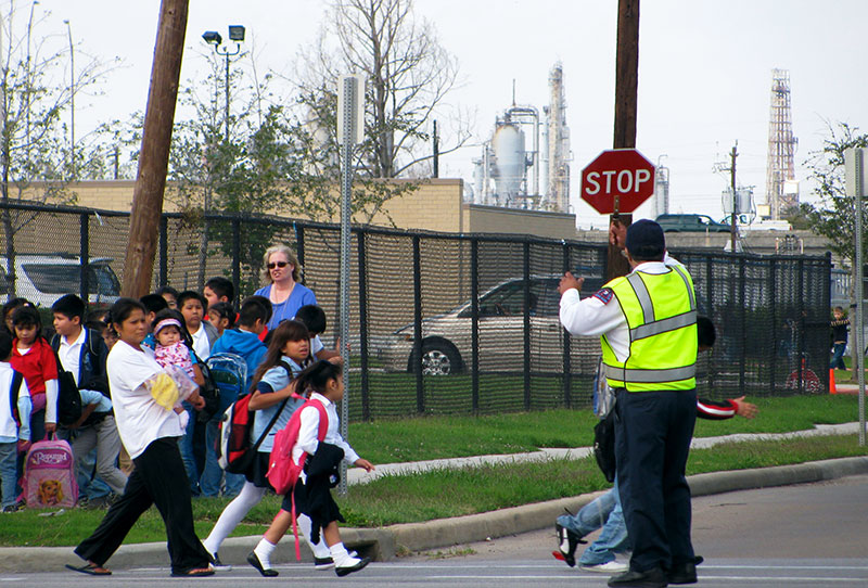 Kids crossing the street with chemical plants in the background