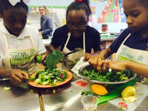 A group of girls mix their salad ingredients.