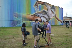 "Houston Public Media's Brandon Alexander, Matt Brawley, Ernie Manouse and Cameron Knott shoot and episode of Arts InSight at the site of Houston's biggest mural, by artist Sebastien ""Mr. D"" Boileau."