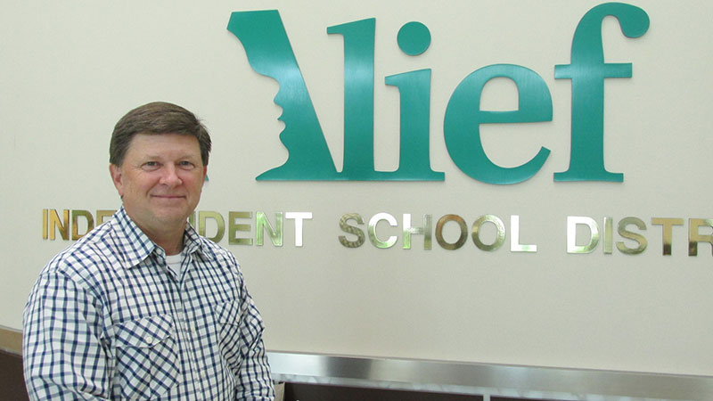 Superintendent HD Chambers stands in front of Alief sign