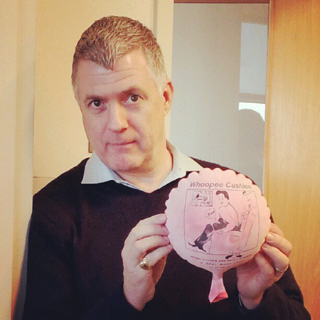 Classical 91.7 program director St. John Flynn with Whoopee cushion. Photo by Dacia Clay.