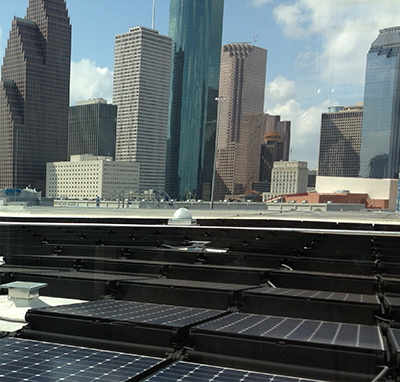 solar panels on roof with view of Houston skyline