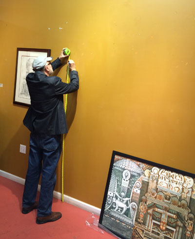 Gus Kopriva hanging a painting