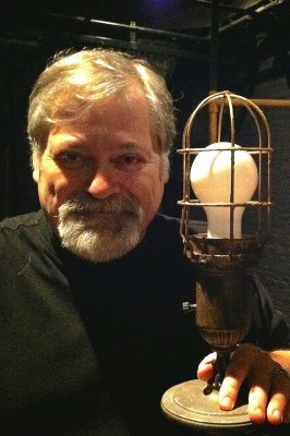 Photo of composer Daron Hagen holding a lamp base.