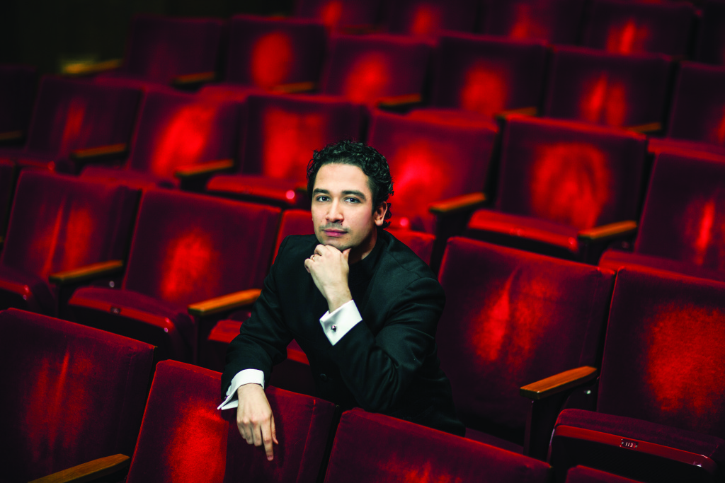 Conductor Andrés Orozco-Estrada sitting in the seats in Jones Hall looking at the camera