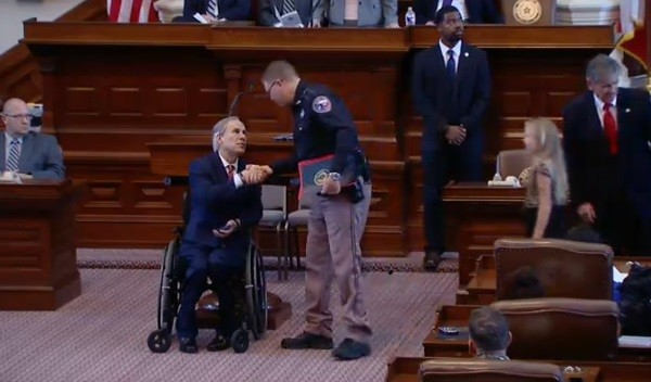 Texas Governor Greg Abbott shakes hands with a law enforcement officers as he presents medals to those who were killed or injured in the line of duty.