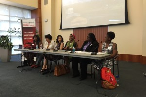 A panel of women sits at a table speaking into microphones about how women's issues fit within the Black Lives Matter movement.