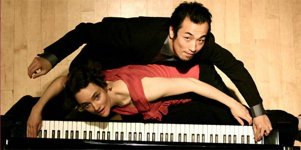 Eva-Maria Zimmerman and Keisuke Nakagoshi of ZOFO pose over a piano keyboard.
