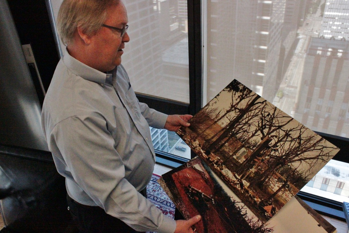 In his office in Houston, lawyer Joseph Garrett holds photo of damage from 1992 explosion