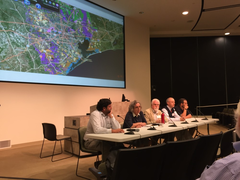 Panelists sit at a table discussing conservation in Houston.
