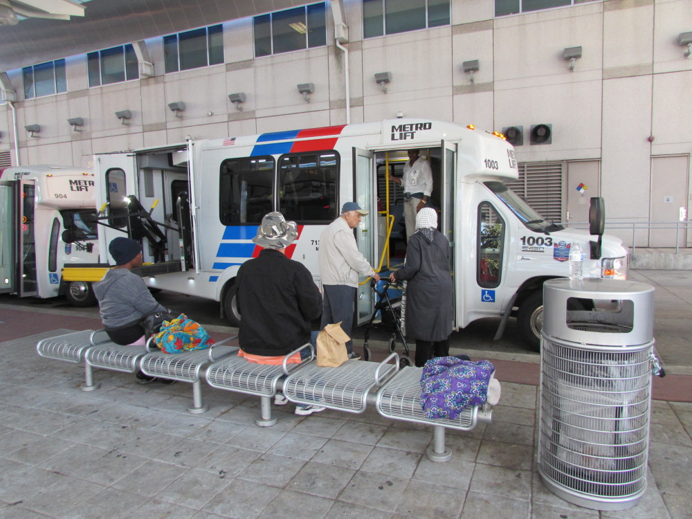 MetroLift customers board paratransit buses outside Metro's downtown headquarters.