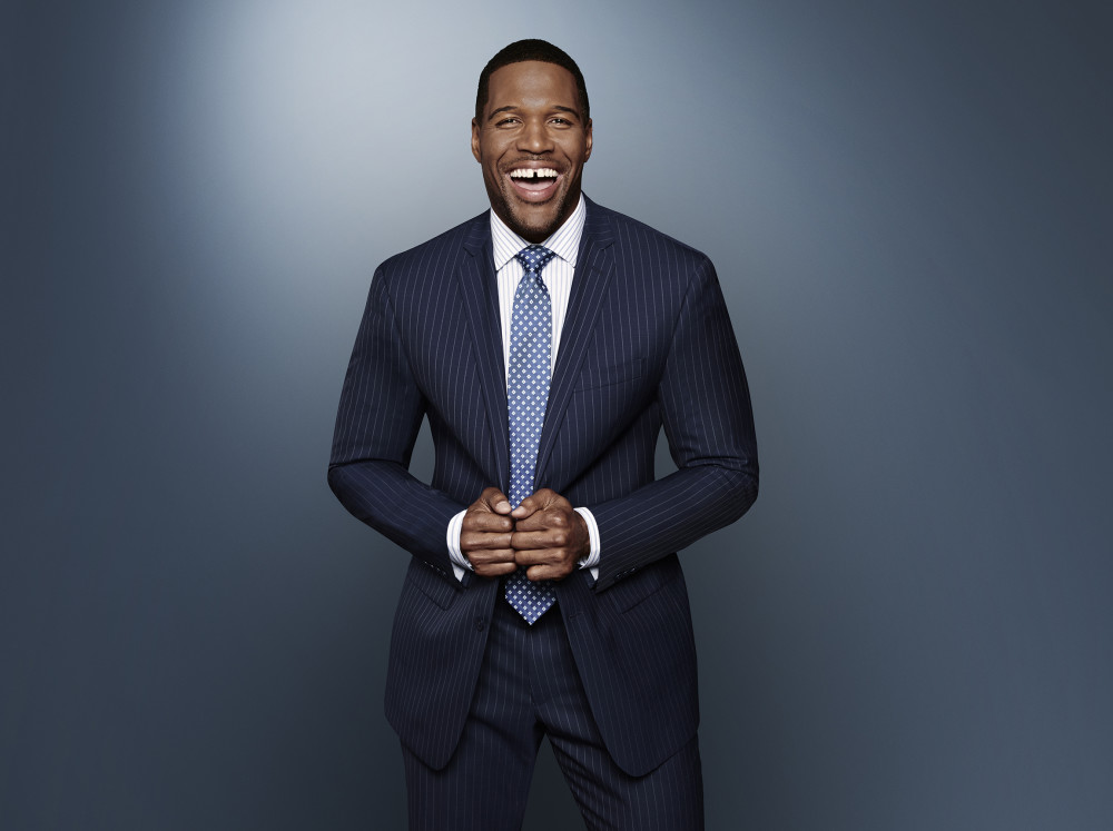 Michael Strahan smiling in navy suit.
