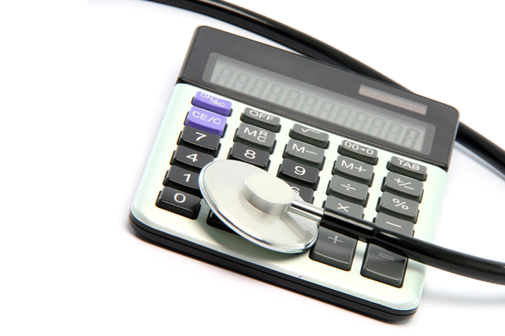 stethoscope on calculator isolated on white background healthcare and finance concepts
