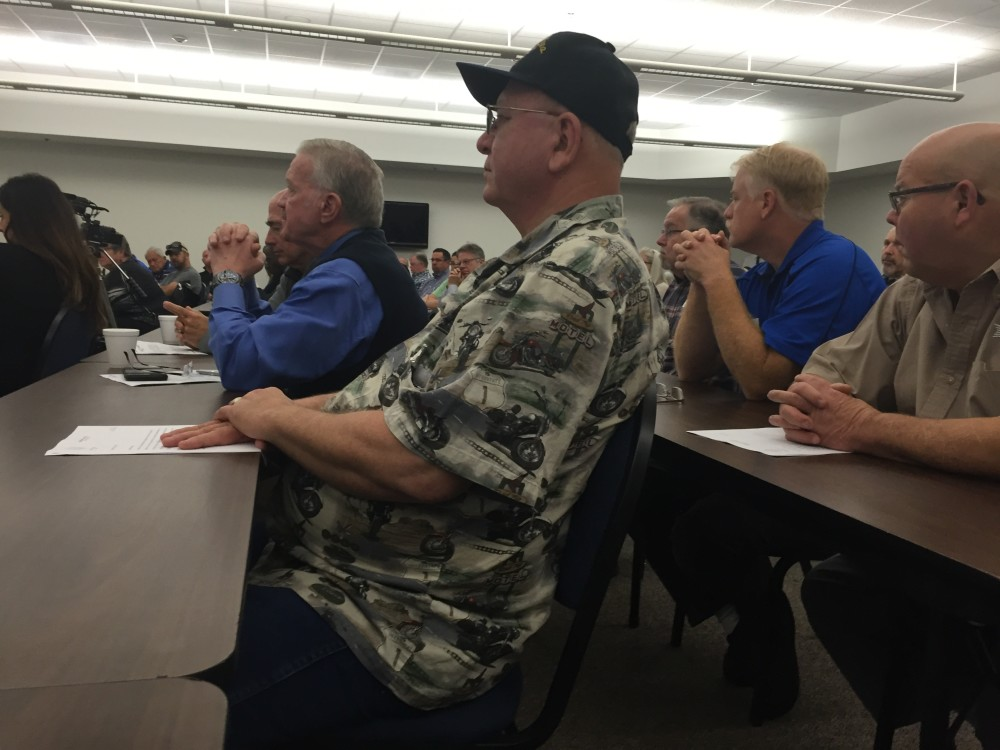 Wilson Stasney sits at a table as the sheriff explains open carry legislation.