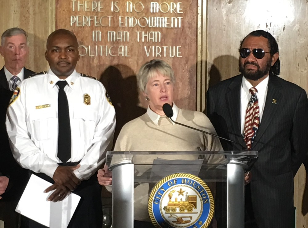 Houston Mayor Annise Parker speaks at a podium during a press conference. She is joined by interim Houston Fire Chief Rodney West (L) and Congressman Al Green (R).