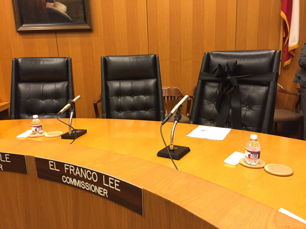 A black ribbon is wrapped around the empty seat of the late Precinct 1 Commissioner El Franco Lee.