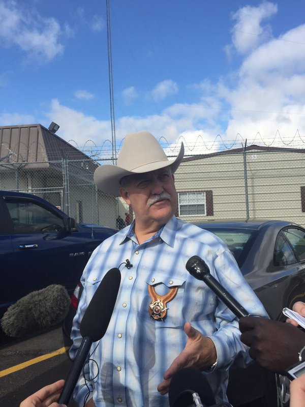 Sheriff in front of held mics