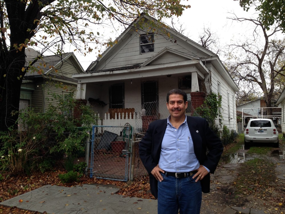 Adrian Garcia poses in front of the house where he grew up, in the North section of Houston.