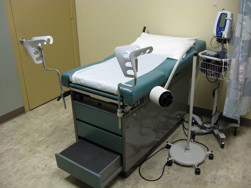 hospital photo of a patient room and gynecological stirrups chair