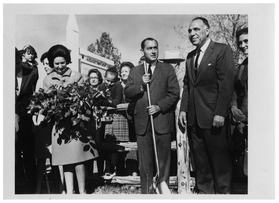 Photograph of Lady Bird Johnson and Henry B. Gonzalez standing by a fence with other people.