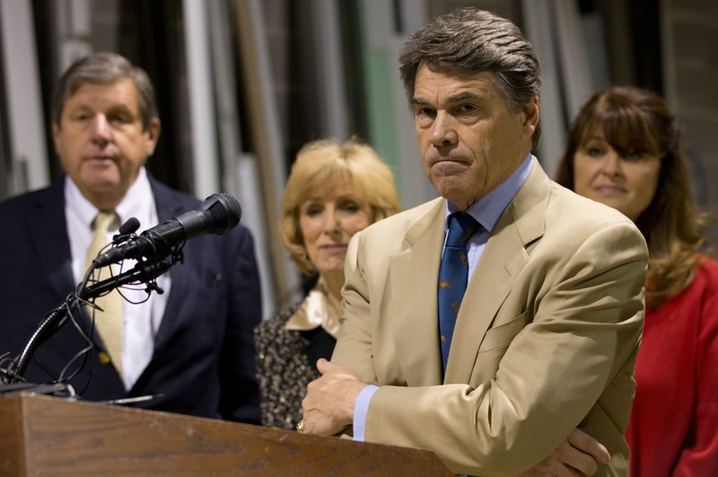 Texas Gov. Rick Perry stands with his arms crossed