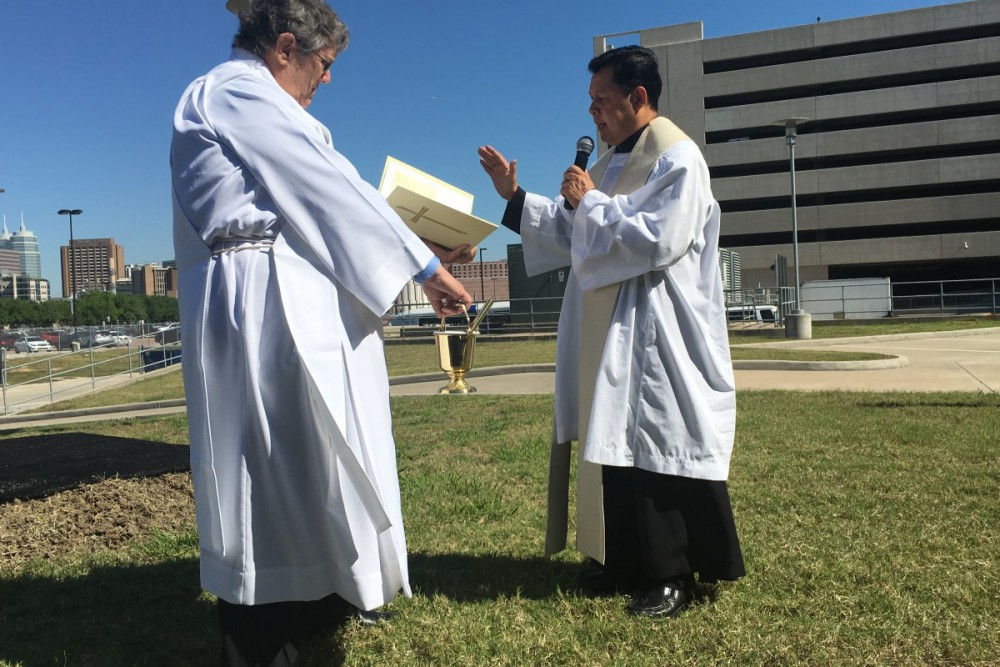 Father Michael Barrosa, chaplain at Baylor St. Luke's Medical Center, sprinkles holy water on the site of the future hospital tower