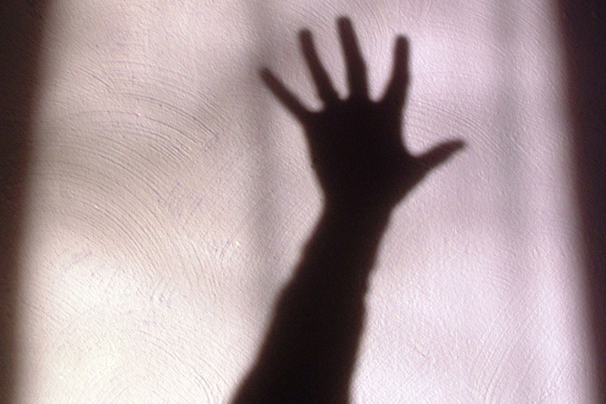 shadow of a woman holding hand up