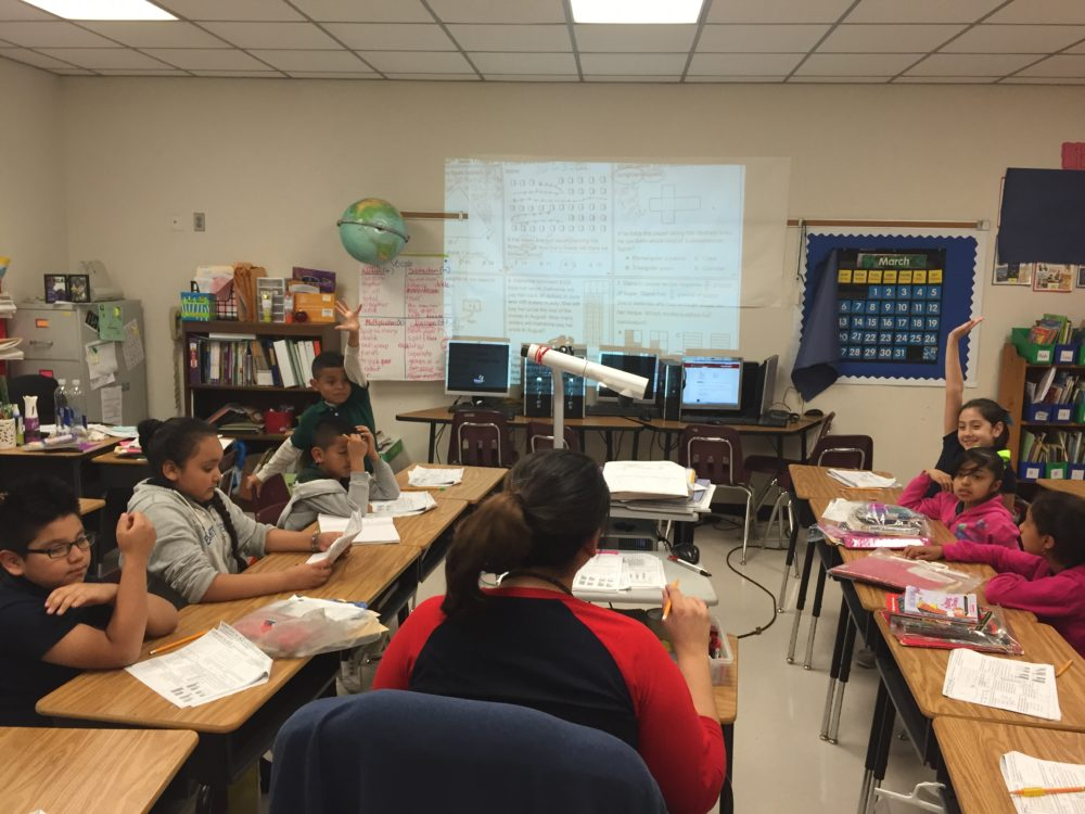 Teacher Melissa Trujillo coaches third grade students in congruent shapes. About 80 percent of students at Bussey Elementary are English language learners.