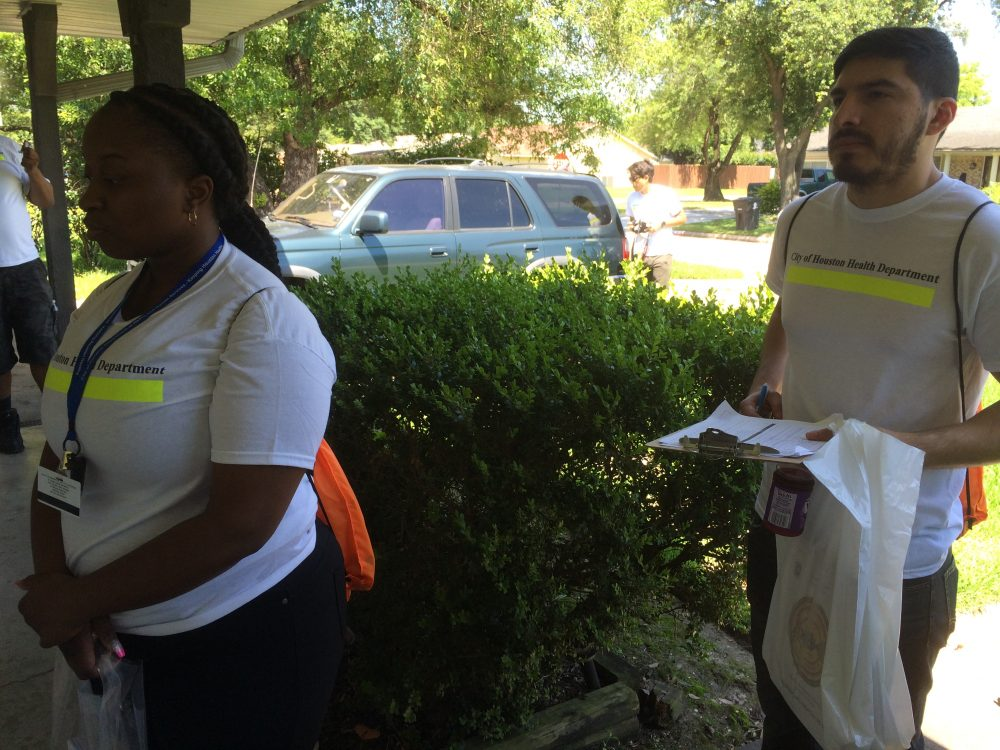 Kalicia Minor and Daniel Perez with the Houston Health Department knock on a door in a northwest Houston neighborhood.