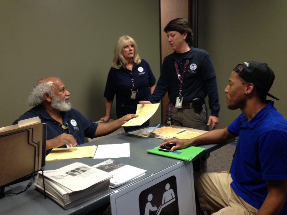 Dante Jones receives assistance from FEMA representative Paul McFarlane at the disaster recovery center the agency has opened in the Greenspoint area.