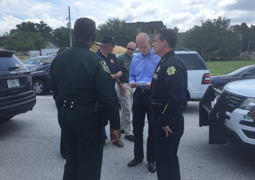 Florida Gov. Rick Scott talks with law enforcement before a briefing about the Sunday morning shooting at Pulse nightclub in Orlando.