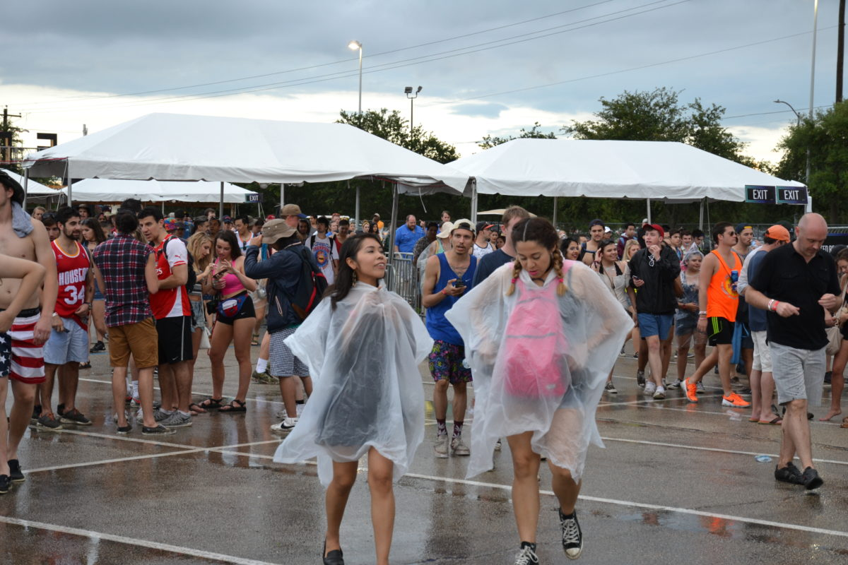 Concert goers brave the rain during the 2016 Free Press Summer Fest, held at the NRG Stadium parking lot for the second year in a row because of severe weather. (Photo: Amy Bishop, Houston Public Media)