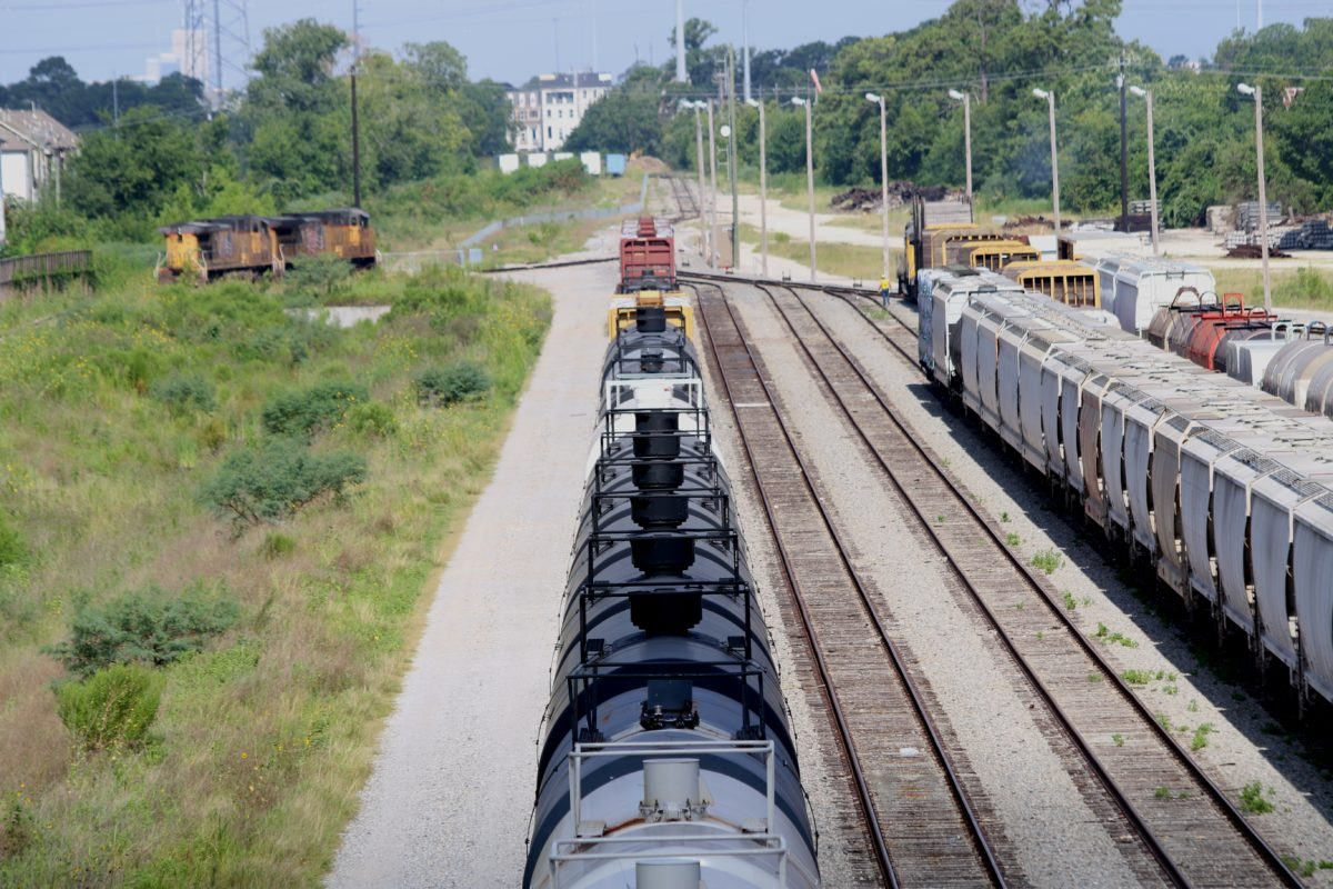 Tank cars for carrying crude oil (the ones painted black) sit on tracks near homes west of downtown Houston. (Photo: Dave Fehling, Houston Public Media)