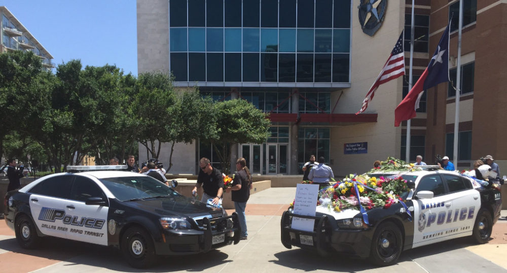 A pair of Dallas Police Department cruisers serve as a memorial for the fallen officers outside of the agency's headquarters.