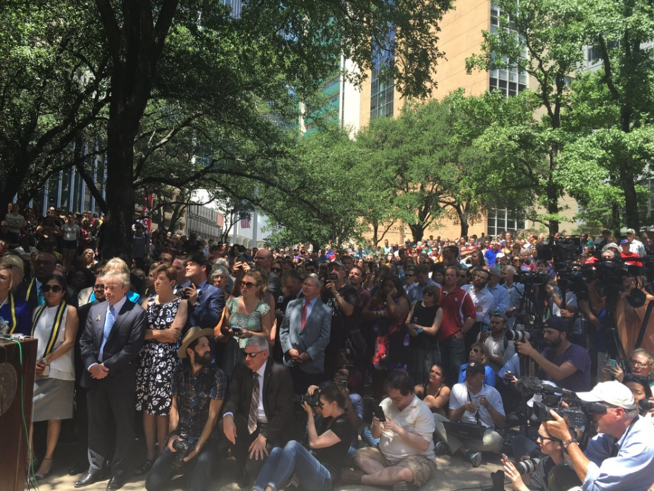 Hundreds gather in downtown Dallas Friday for a prayer vigil for the five police officers killed and those hurt in a mass shooting Thursday night.