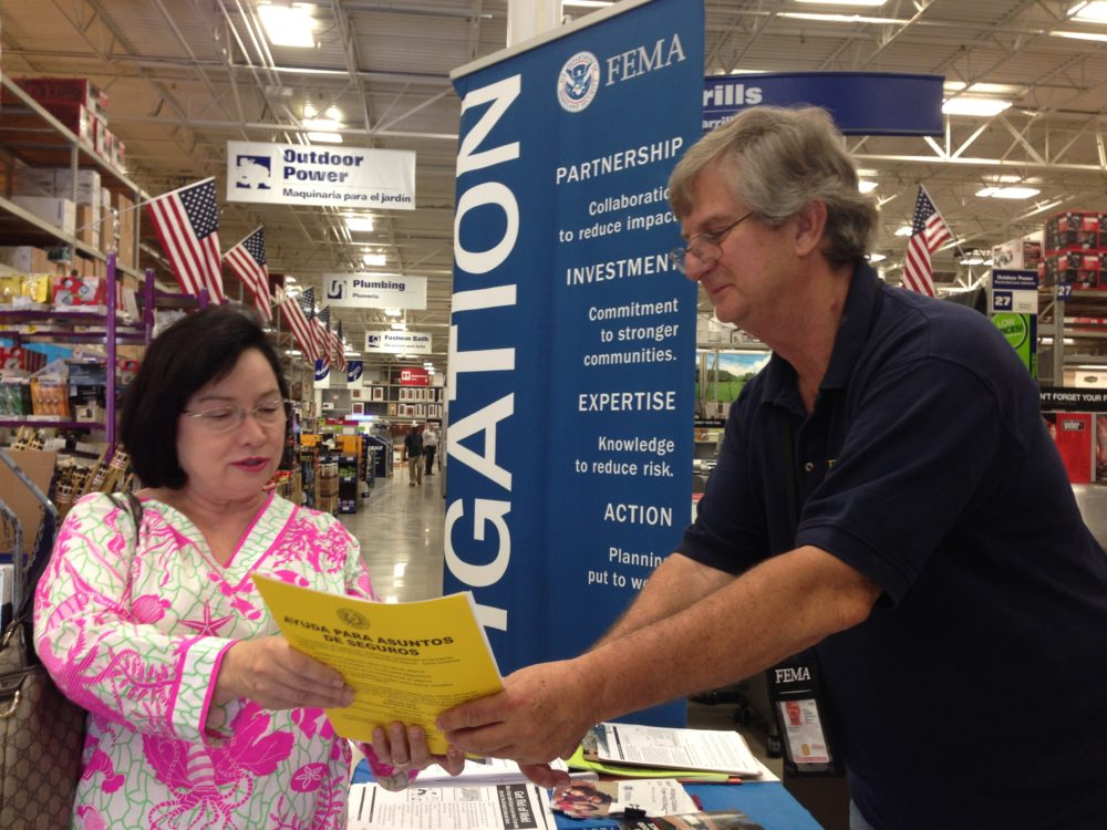FEMA disaster mitigation specialist Kenneth Milausnic shows Sugarland resident Margie Phillips a brochure about how to reduce the effects of flooding in homes.