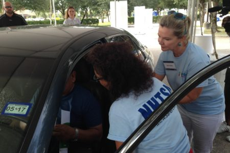 NHTSA workers check the car of Houston resident who decided to dropped by their community event.