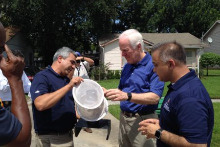 Doctor Mustapha Debboun, director of Harris County's Mosquito and Vector Control, U.S. Senator John Cornyn, and Doctor Umair Shah, executive director of Harris County Public Health examine a mosquito trap in a south Houston neighborhood.