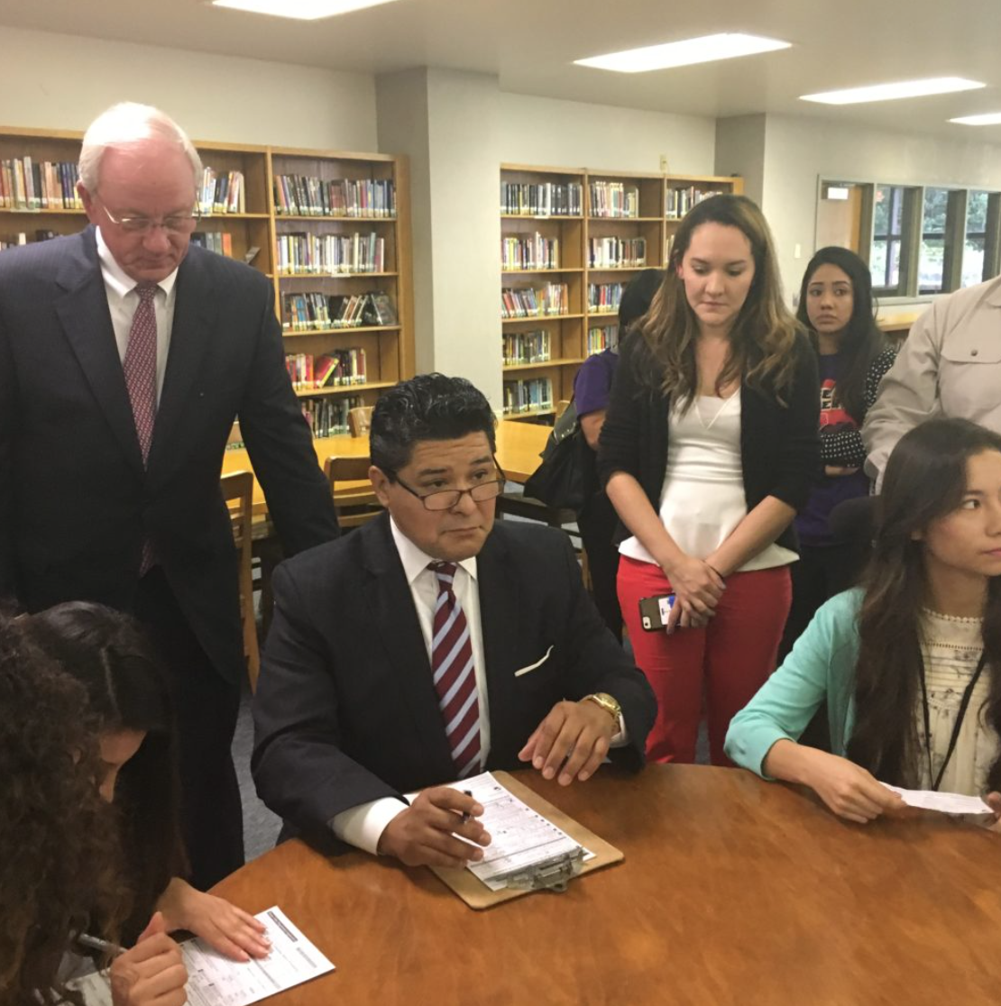 Richard Carranza, Houston ISD Superintendent, a recent arrival from California, registers as a Texas voter alongside students at Sam Houston Math, Science, and Technology Center. Mike Sullivan, Harris County Tax Assessor-Collector, looks on.