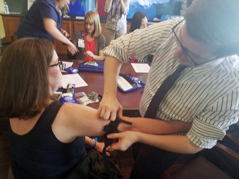 "Michael Overton fastens a tourniquet onto coworkers, Amanda Stallings, during ""Stop the Bleed"" training in Fort Worth."