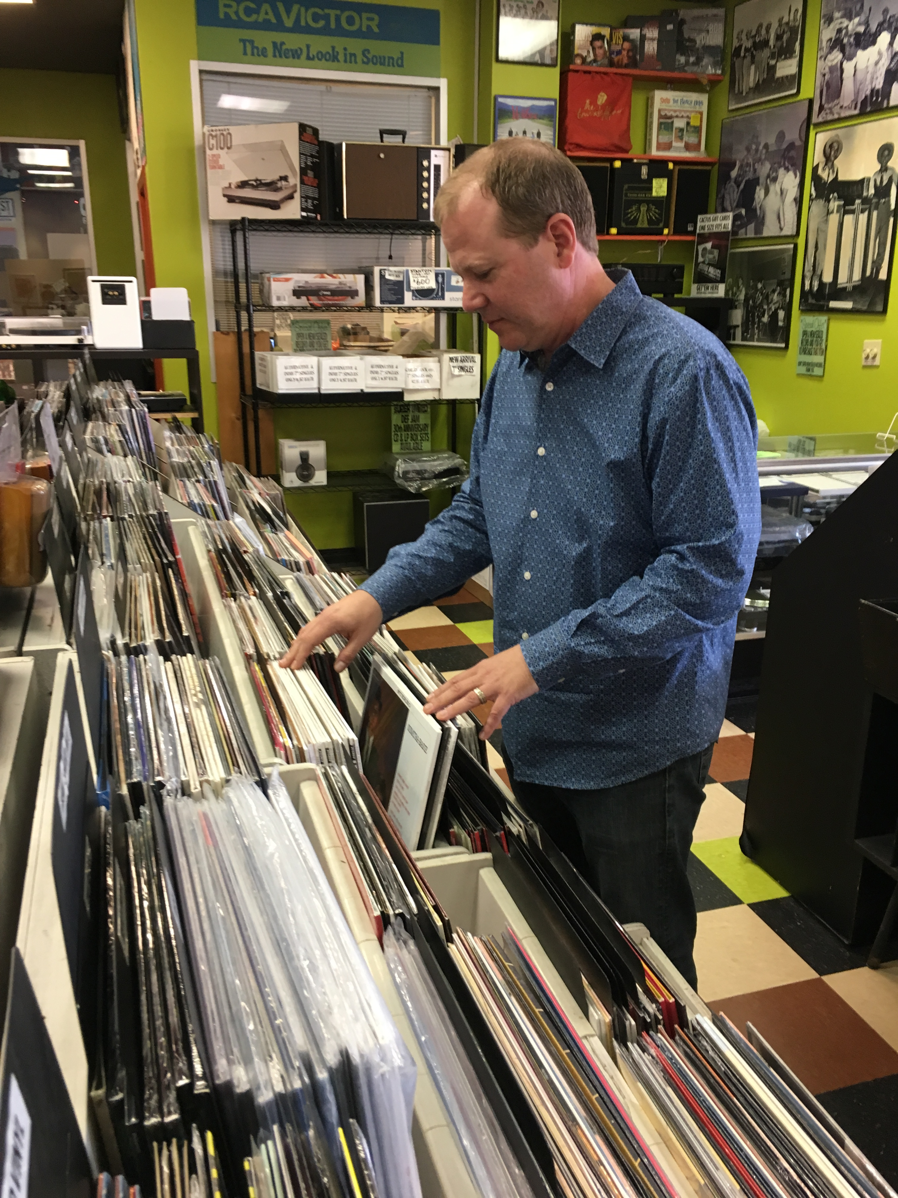 Quinn Bishop from Cactus Music looks through the store's collection of vinyl records – a format that's enjoying a resurgence.