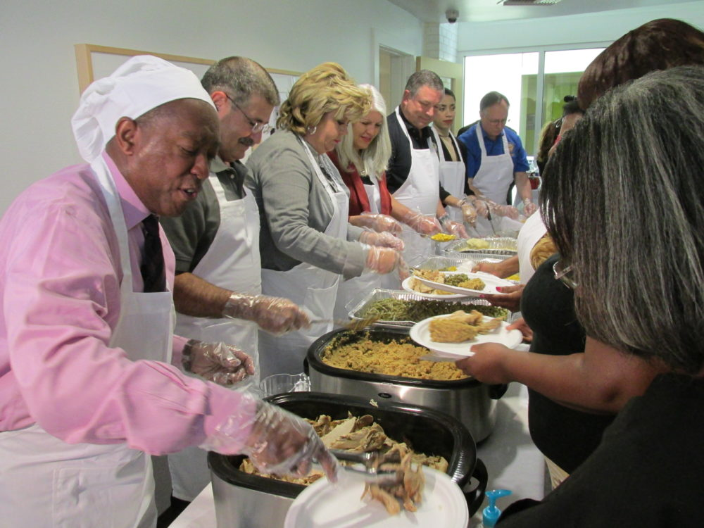 Mayor Sylvester Turner and council members Mike Knox, Brenda Stardig, Karla Cisneros, Greg Travis, Amanda Edwards and Mike Laster (from left) serve turkey and sides to resident of New Hope Housing's Rittenhouse complex near Acres Homes.