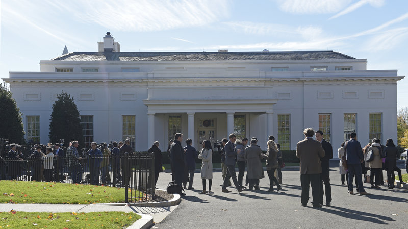 People gather outside the West Wing of the White House Thursday, as they wait for the arrival of President-elect Donald Trump for his meeting with President Obama.