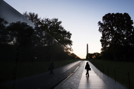 A visitor walks along a wall of names at the Vietnam War Memorial early in the morning, Tuesday, Oct. 25, 2016, in Washington. (AP Photo/J. David Ake)