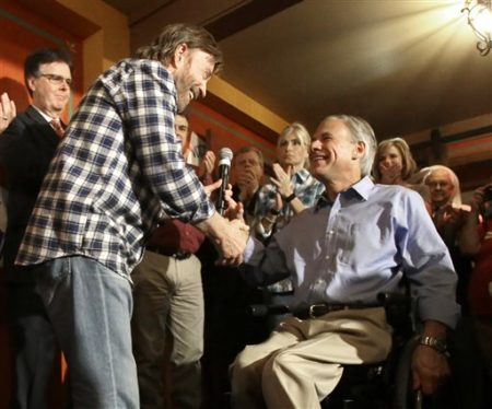 Texas Republican gubernatorial candidate Greg Abbott, right, shakes hands with actor Chuck Norris as Dan Patrick, left, candidate for Lt. Gov. looks on at a campaign event, Monday, Nov. 3, 2014, in Houston.