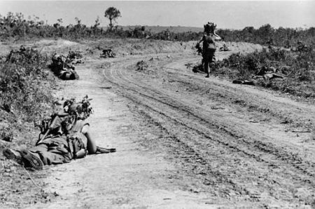 U.S. Marines of the 2nd Battalion lie in the dirt alongside Road 561 as one of them is running around the curve to get into better fireposition, near Cam Lo, South Vietnam, May, 19, 1967.