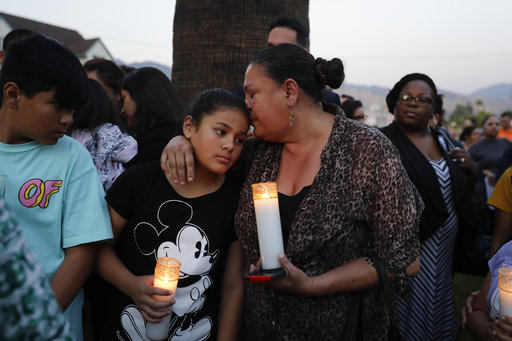 Betty Rodriguez, right, comforts her granddaughter Giselle, 11, during a prayer service held to honor the shooting victims at North Park Elementary School, Monday, April 10, 2017, in San Bernardino, Calif. A man walked into his estranged wife's elementary school classroom in San Bernardino and opened deadly fire on Monday.