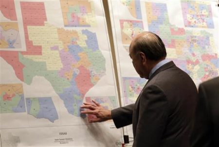 "May 30, 2013 file photo, Texas state Sen. Juan ""Chuy"" Hinojosa looks at maps on display prior to a Senate Redistricting committee hearing in Austin, Texas."